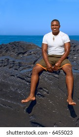 Portrait of African-American male sitting on cliff