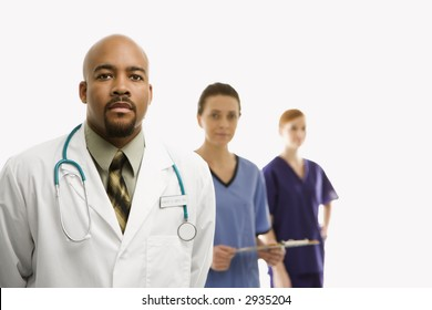 Portrait of African-American man and Caucasian women medical healthcare workers in uniforms standing against white background.