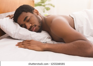 Portrait of african-american man sleeping naked on stomach in bed at home, closeup