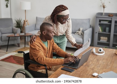 Portrait of African-American man using wheelchair working from home with wife looking over his shoulder, copy space