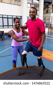 Portrait of African-american physiotherapist helping disabled African-american man walk with prosthetic leg on ramp in sports center. Sports Rehab Centre with physiotherapists and patients working