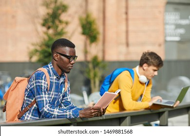 Portrait of African-American student reading book outdoors in sunlight, copy space