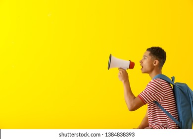 Portrait of African-American teenage boy with megaphone on color background