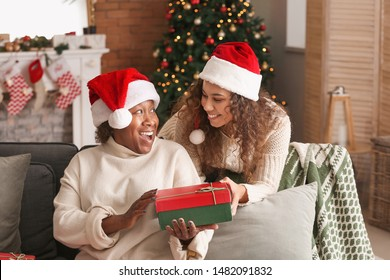 Portrait of African-American woman and her daughter with Christmas gift at home