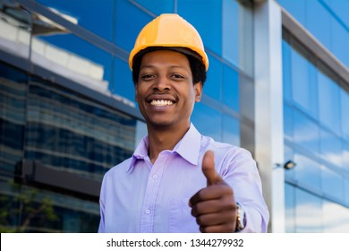 Portrait of Afro american engineer developer in hard hat giving thumb up.