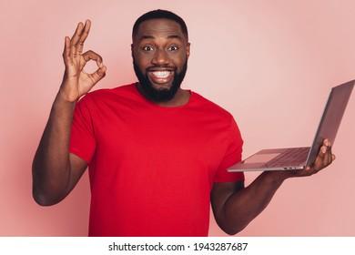 Portrait of afro american man using laptop show okey symbol