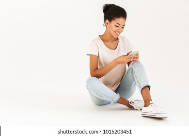 Portrait of afro american woman in casual sitting on floor with legs crossed and using mobile phone isolated over white background