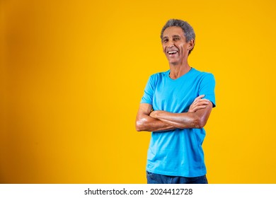 Portrait of afro elderly man with arms crossed smiling at the camera.