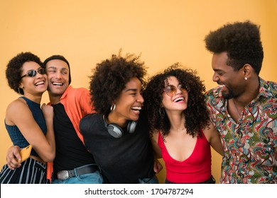 Portrait of Afro friends having fun together and enjoying good time against yellow background. Friendship and lifestyle concept.