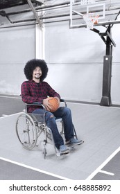 Portrait of Afro man smiling at the camera while sitting in a wheelchair with basketball