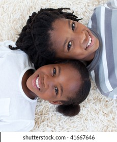 Portrait of Afro-American brother and sister on floor with heads together