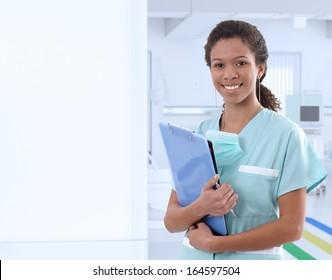 Portrait of afro-american female nurse at hospital corridor, smiling. Large copyspace on left.