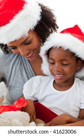 Portrait of an Afro-American mother and daughter opening a Christmas gift