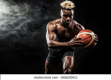 Portrait of afro-american sportsman, basketball player with a ball over black background. Fit young man in sportswear holding ball.