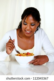 Portrait of an afro-american woman eating a bowl of cereals with strawberries at soft colors composition