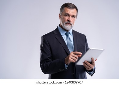 Portrait of aged businessman wearing suit and tie. Businessman in years standing on white background. Boss using tablet computer