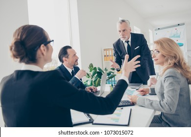 Portrait of aged displeased senior is out of himself, he did not find a resolution agreement with his partner gesturing with hand standing near desk, gathering in workplace, workstation