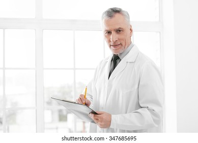 Portrait of aged doctor wearing lab coat. Doctor in years standing in hospital office with big window. Medico holding folder and looking at camera
