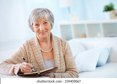 Portrait of aged female with notepad looking at camera with smile