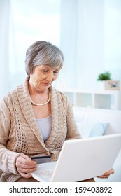 Portrait of aged female shopping through internet