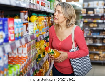 Portrait of aged woman choosing refreshing drinks on shelves in grocery shop