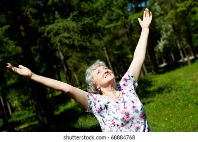 Portrait of aged woman with her arms raised in praise