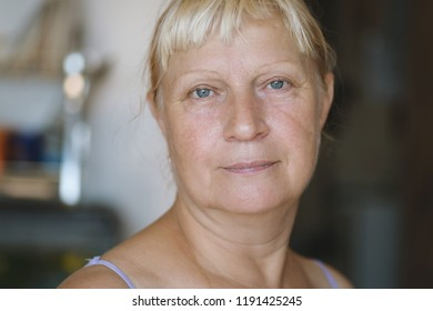 Portrait of a aged woman at the kitchen. Selective focus with shallow depth of field.