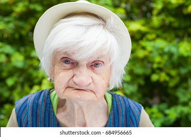 Portrait of an aged woman sitting outdoor in the garden on summertime