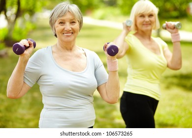 Portrait of aged women doing physical exercise with barbells