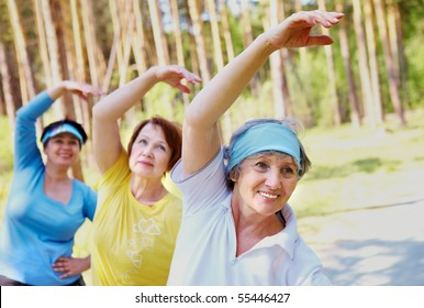 Portrait of aged women with their arms raised while doing physical exercise