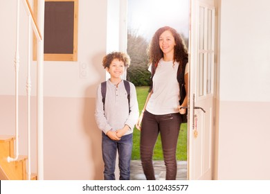 Portrait of age-diverse children, smiling boy and girl with backpacks, coming back home from school