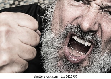 portrait of a aggressive crying man with a clenched fist, open mouth snd  grey full beard, concept for violence, hate and aggression