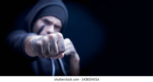 Portrait of aggressive man giving a punch. Robbery and konflict concept. Selective focus on fist.