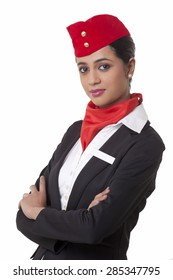Portrait of air hostess with arms crossed standing against white background