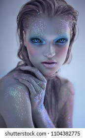 Portrait of alien woman with glitter make up looking at camera