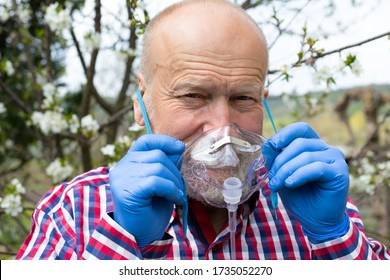 Portrait of allergic senior man holding oxygen mask , standing in front of blooming apple tree