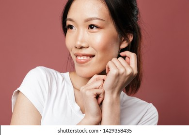 Portrait of alluring asian woman dressed in basic wear smiling and looking aside isolated over red background in studio