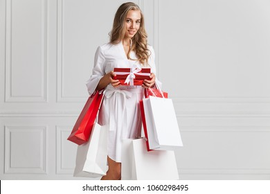 Portrait of alluring woman with nice long hair and delicate makeup standing in white dress with  presents and papper bags. Charming lady in stylish dress looking at camera with happiness and calmness