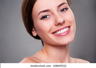 portrait of alluring young woman smiling and looking at camera over grey background