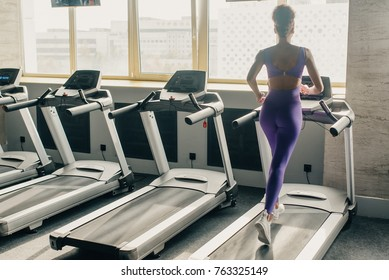 Portrait of alone young adult happy woman with long flying hair running on treadmill in gym wearing in sexy violet suit. Slim sport body.