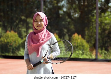 portrait of amateur hijab female tennis player with head scarf holding tennis racket standing at outdoor hard court tennis field on a bright day