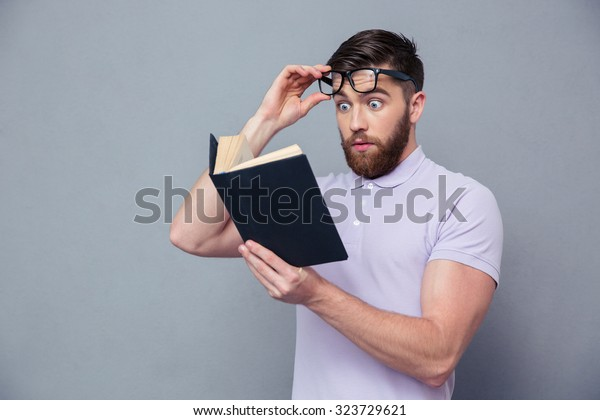 Portrait of amazed casual man reading book over gray background