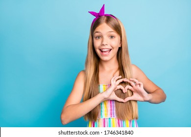 Portrait of amazed energetic cheerful kid girl make heart shape finger demonstrated cupid love symbol chest wear trendy clothes isolated over blue color background
