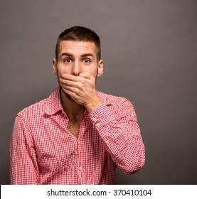 Portrait of amazed man covering his mouth over grey background, copyspace on the side.