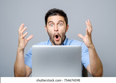 Portrait of amazed man with laptop computer over gray background