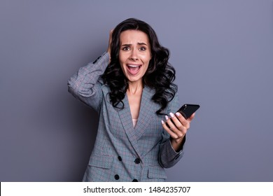 Portrait of  amazed person with curly hairstyle touching her head yelling omg wearing jacket blazer isolated over grey background