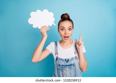 Portrait of amazed person holding paper card bubble screaming wow wearing white t-shirt denim jeans overalls isolated over blue background