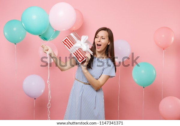 Portrait of amazed pretty young woman wearing blue dress looking on red box with gift present holding colorful air balloons on pink background. Birthday holiday party, people sincere emotions concept