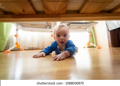 Portrait of amazed toddler boy lying on floor and looking under the bed