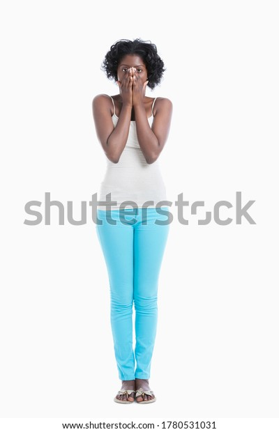 Portrait of an amazed young woman with hands over mouth standing against white background